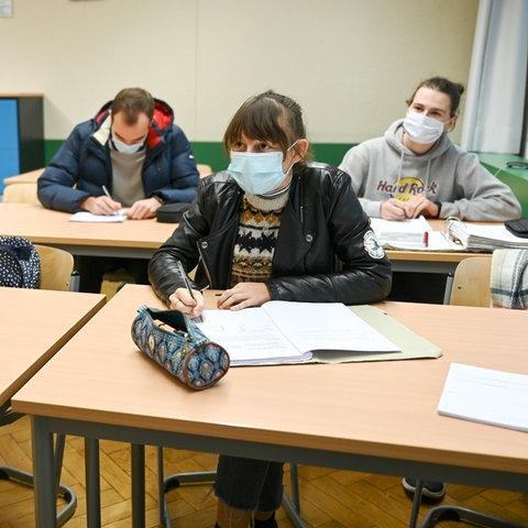 Schülerinnen und Schüler sitzen mit Mundschutz im Unterricht