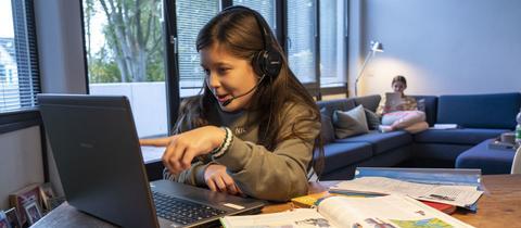 Ein Mädchen sitzt mit einem Headset am Computer an einem Tisch im Wohnzimmer. Vor ihr Schulbücher, im Hintergrund sitzt ein weiteres Mädchen mit Büchern auf einer Couch.