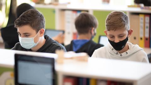 Schülerinnen und Schüler sitzen mit Gesichtsmasken bekleidet im Klassenraum vor einem Computer.