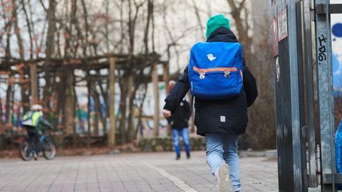 Ein Schüler rennt mit Schultasche über den Pausenhof.