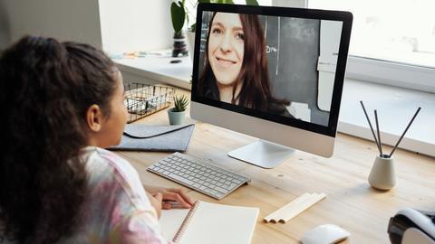 Ein Mädchen sitzt an ihrem Schreibtisch vor dem Bildschirm, auf dem die Lehrerin zu sehen ist.