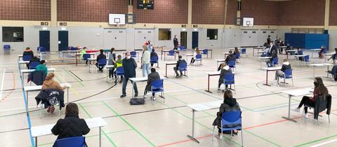 Schülerinnen und Schüler sitzen mit zwei Metern Abstand an Tischen in der Turnhalle.