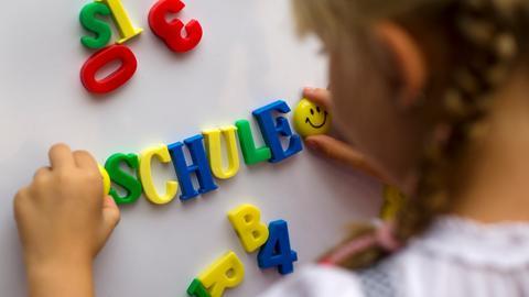 """Ein Mädchen bildet mit Magnetbuchstaben das Wort """"Schule"""" an einer Wand."""