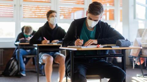 Schüler sitzen im Klassenraum an Schreibtischen während des Unterrichts.