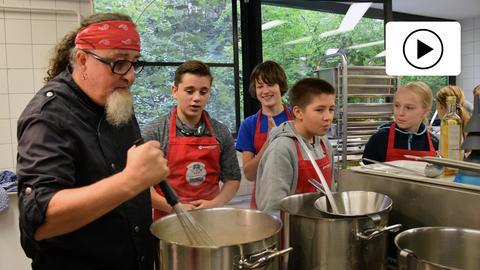Stefan Marquard mit Schülern in Schulküche