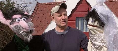 """Jan Kuhl, der """"Schulfritz"""", hält mit zwei selbstgefertigte Handspielpuppen hoch."""