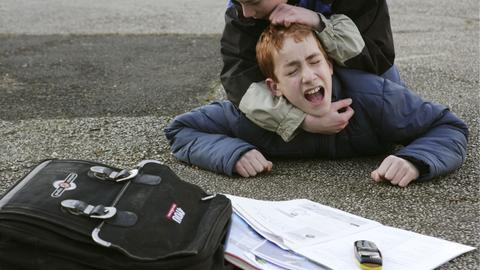 Ein Schüler schlägt einen anderen Schüler