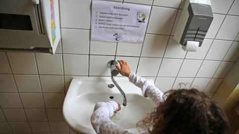 """In Mädchen steht an einem Waschbecken in einer Schultoilette. An der Wand zu lesen die """"Kloordnung"""""""