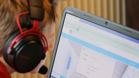 Eine Junge sitzt vor einem aufgeklapptem Laptop und macht Homeschooling, auf dem aufgeklapptem Laptop ist die Anmeldeoberfläche vom Schulportal Hessen zu sehen.