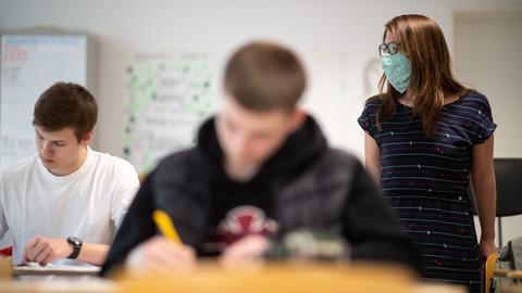 Lehrerin geht mit Maske durch die Reihen