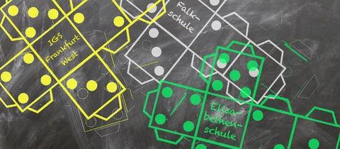 Vorlagen für Würfel zum Selbstbau liegen auf einem Tafelhintergrund. Anstelle der 6 sind Namen der am meisten gewünschten Schulen zu lesen.