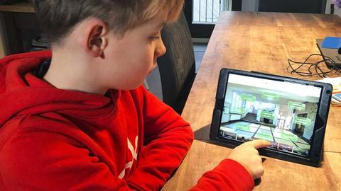 Teo Brandenburger schaut sich auf einem Tablet die Vorstellungsseite seiner Wunschschule an.