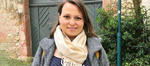 Portrait von Claudia Schmitz vor einem alten Gebäude stehend.