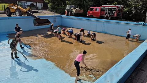 Menschen, die ein halbleeres Schwimmbad mit Schaufeln vom Matsch befreien