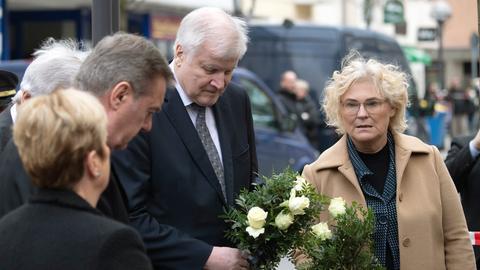 Christine Lambrecht (SPD), Bundesjustizministerin, und Horst Seehofer (CSU), Bundesinnenminister, stehen am Heumarkt in unmittelbarer Nähe eines Tatortes mit Blumen in den Händen.
