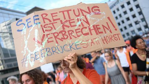 """Demonstranten in Frankfurt halten ein Schild mit der Aufschrift : """"Seenotrettung ist kein Verbrechen"""" hoch."""