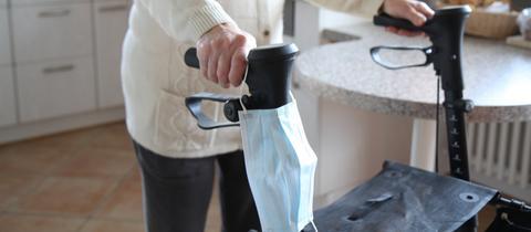 Eine Seniorin hat eine Maske an ihren Rollator gehängt.