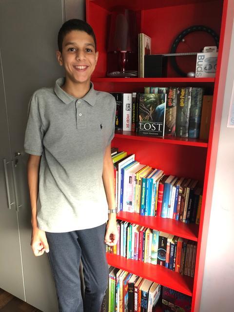 Shadi Rassiane vor seinem Bücherregal