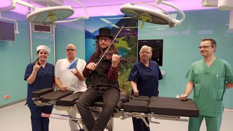 Mitarbeiterinnen und Mitarbeiter sitzen auf einem OP-Tisch, einer hält eine Geige in der Hand.