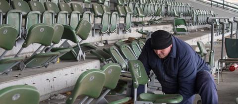 Ein Mann demontiert ausgediente Sitze auf der Tribüne der ehemaligen Galopprennbahn.