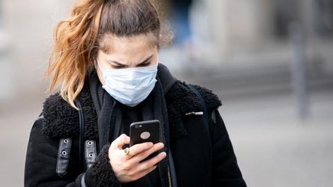 Frau mit Mundschutz schaut auf Handy