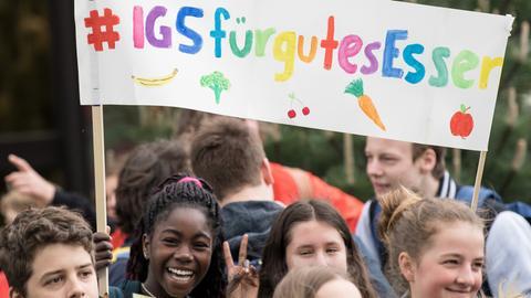 """Schüler halten auf einer Demo vor dem Sitz des Groß-Caterers Sodexo ein Plakat mit der Aufschrift """"#IGS für gutes Essen""""."""