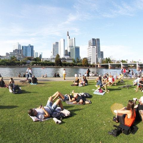 Personen genießen die warme Sonne und den Spätsommertag auf der Liegewiese am Mainufer vor dem Bankenviertel in Frankfurt