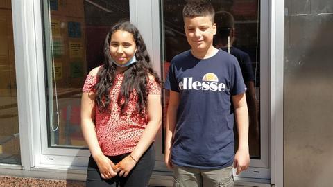 """Die Protagonisten Ilham und Luca stehen vor dem Gebäude der """"Arche""""."""