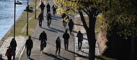 Spaziergänger, Fahrradfahrer und Jogger sind am späten Nachmittag am Main unterwegs.