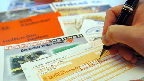 Zu sehen ist eine Hand, die mit einem Kugelschreiber einen gelben Überweisungsträger ausfüllt. Darunter liegen auf einem Tisch zahlreiche Broschüren von wohltätigen Organisationen.