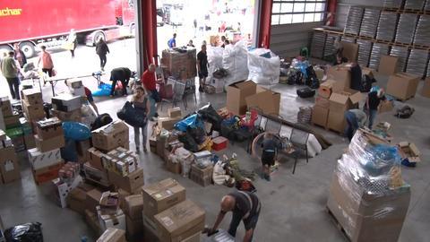 Blick von oben in eine Lagerhalle, in der Menschen viele Kisten und Kartons stapeln