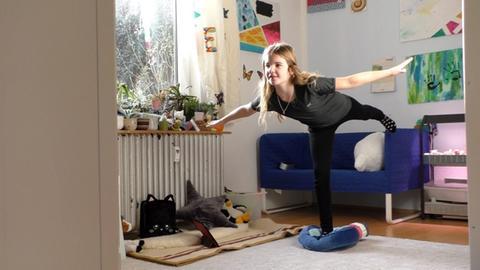 Luzie macht in ihrem Kinderzimmer Sport vorm Tablet.