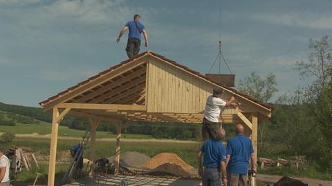 Ehrenamtliche bei der Arbeit im künftigen Natur-Erlebniszentrum in Ortenberg beim Aufbau einer Holzhütte.