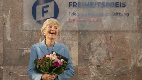 """Friede Springer steht vor einem Banner mit der Aufschrift """"Freiheitspreis""""."""