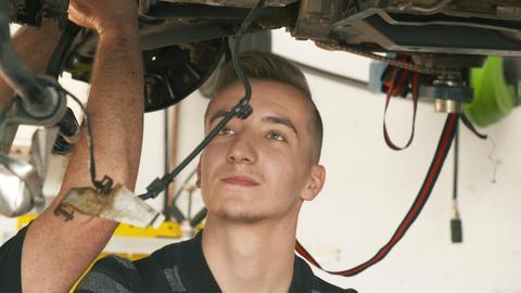 KFZ-Azubi Lukas steht unter einem Auto