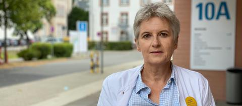 Sabine Wicker steht im Arztkittel vor einem Krankenhauseingang.