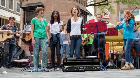 Eine Gruppe von Jugendlichen singt und spielt Instrumente in einer Fußgängerzone.