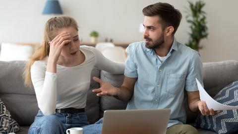 Ein Paar sitzt auf einer Couch, vor sich einen Laptop. Beide schauen angespannt.