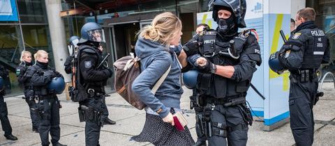 Ein Polizist führt eine Studentin aus dem Audimax der FH Frankfurt.