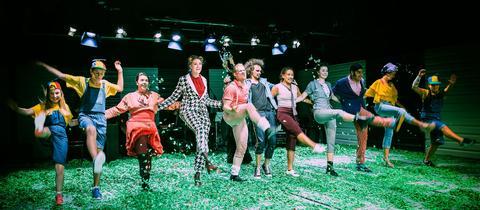 Menschen in bunten Kleidern tanzen auf der Bühne in einer Reihe.