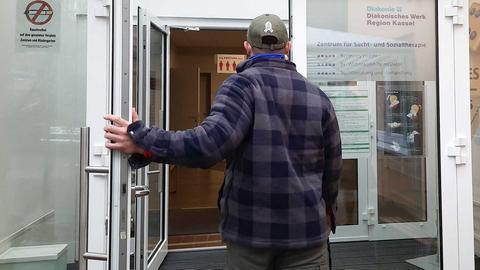 Ein Mann öffnet die Tür zur Suchtberatung der Diakonie in Kassel.