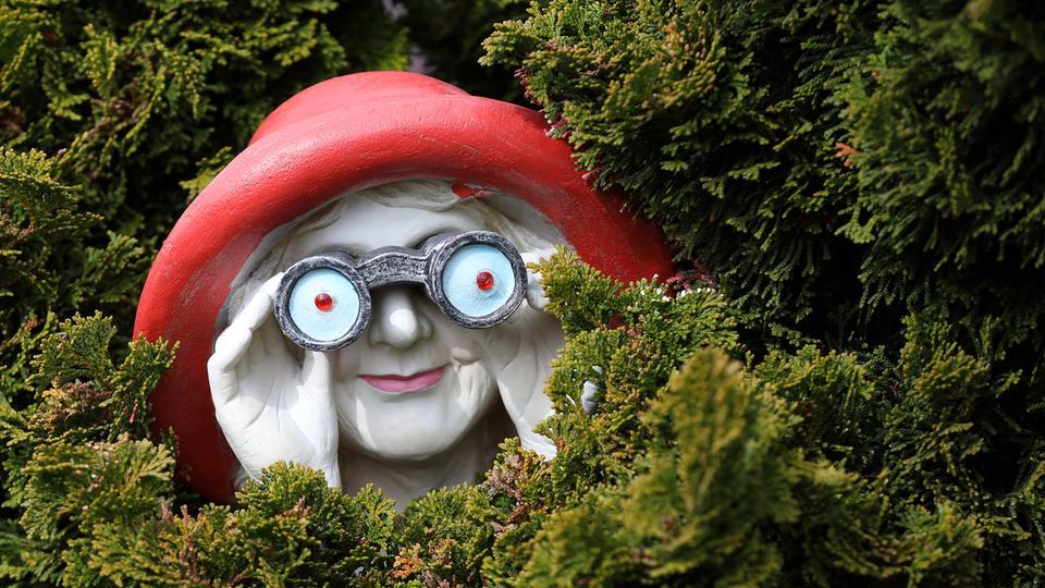 Eine Plastik lugt aus einem Gebüsch hervor. SIe stellt eine Frau dar, die einen roten Hut trägt und durch ein übergroßes Fernglas wohl andere Menschen beobachtet.