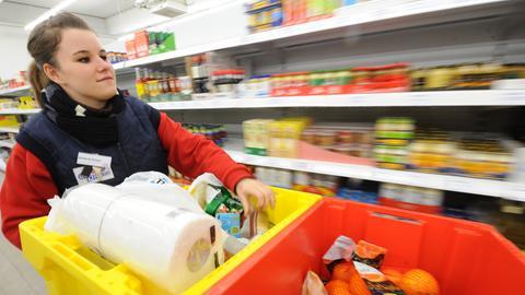 Eine Supermarkt-Mitarbeiterin räumt Regale ein.