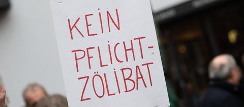 """Eine Demonstrantin fordert vor dem Frankfurter Dom """"Kein Pflicht Zölibat""""."""