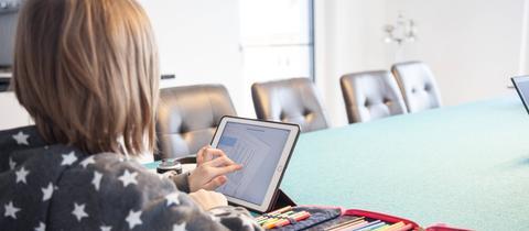 Ein Schüler sitzt vor einem Tablet