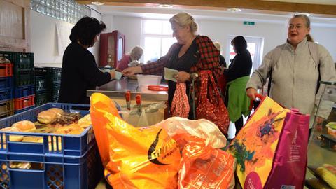 Bedürftige Menschen erhalten in einer Ausgabestelle einer Tafel Lebensmittel.