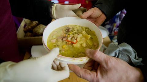 Übergabe von einem Teller Suppe.