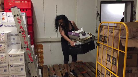 Eine ehrenamtliche Helferin beseitigt beschädigte Kartonagen im überfluteten Keller der Offenbacher Tafel