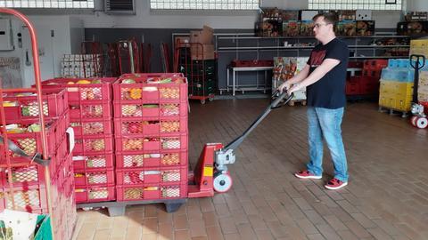 ein Mitarbeiter der Tafeln transportiert Lebensmittelkisten