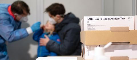 Ein DRK-Helfer führt in einer Teststation einen Corona-Schnelltest an einem Kind durch. Im Vordergrund ist eine Packung mit Antigen-Tests zu sehen.
